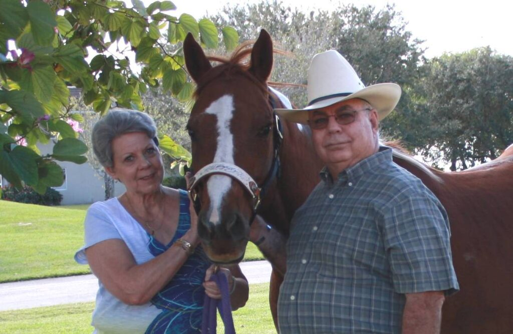 Man in cowboy hat with horse and wife